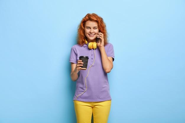 Schöne fröhliche frau hat lustige unterhaltung, benutzt modernes handy, trinkt kaffee zum mitnehmen
