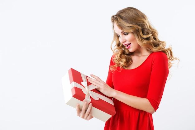 Schöne fröhliche frau im roten kleid mit einem geschenk