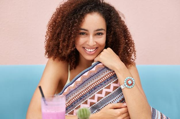 Schöne fröhliche frau mit afro-frisur, hält weiches kissen, hat spaß allein in gemütlichem restaurant, genießt sommergetränk, lächelt freudig, sitzt an rosa wand.
