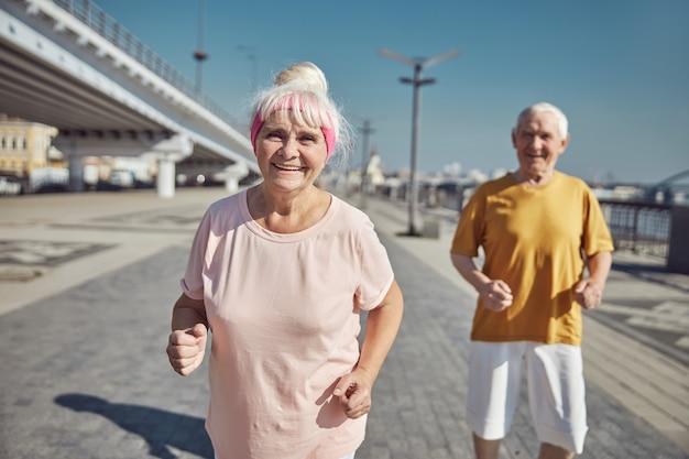 Schöne fröhliche frau und ihr älterer grauhaariger ehemann, die während des trainings in die kamera lächeln