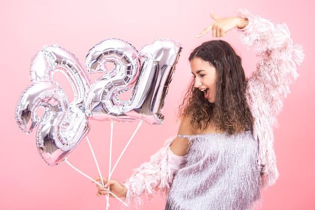 Schöne fröhliche junge brünette mit lockigem haar festlich gekleidet auf einem rosa hintergrund, der souverän mit silbernen luftballons für das neujahrskonzept aufwirft