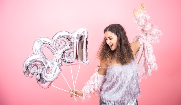 Schöne fröhliche junge brünette mit lockigem haar festlich gekleidet auf einer rosa wand mit warmem licht, das mit silbernen luftballons für das neujahrskonzept aufwirft