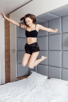 Schöne fröhliche junge frau, die seidenpyjamas trägt, die tanzen und auf das bett springen, nachdem sie am morgen aufwachen