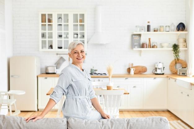 Schöne fröhliche kaukasische hausfrau im eleganten kleid posiert im wohnzimmer, sitzt auf der rückseite der großen grauen couch, lächelt und zeigt ihnen ihre geräumige gemütliche wohnung. ältere menschen und lebensstil