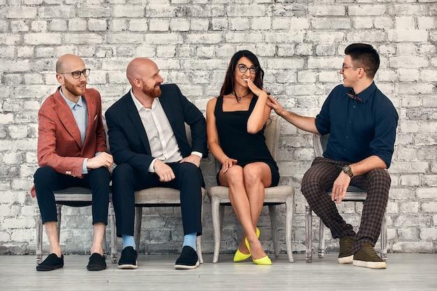 Schöne fröhliche professionelle frau, die brillen trägt, die mit männlichen mitarbeitern und teamleiter im konferenzraum bei der arbeit sitzen.