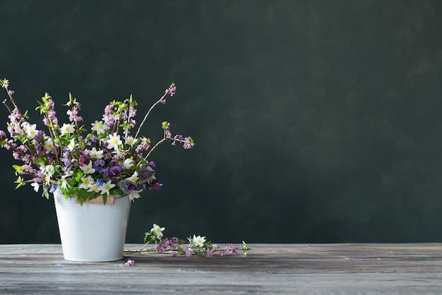 Schöne frühlingsblumen auf dunkler hintergrundwand