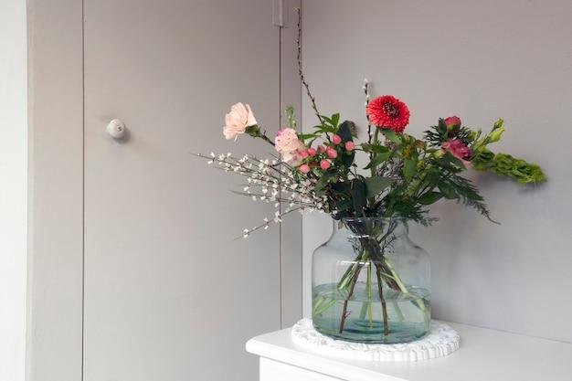 Schöne frühlingsblumen in glas eine vase in der nähe einer grauen wand in einer stilvollen modernen inneneinrichtung