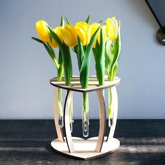 Schöne frühlingsgelbe blumen in einer hölzernen vase mit glasreagenzgläsern