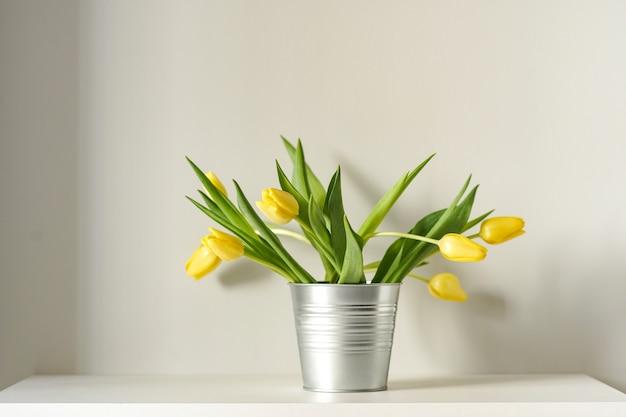 Schöne frühlingsgelbe tulpen im metallischen eimer
