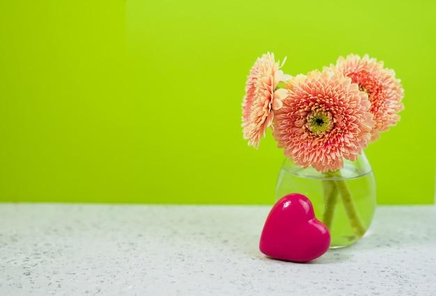 Schöne frühlingsrosablumen auf blauer pastelltabelle in einem vase. blumengrenze
