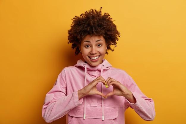 Schöne fürsorgliche frau formt herzgeste, lächelt positiv, gesteht in liebe