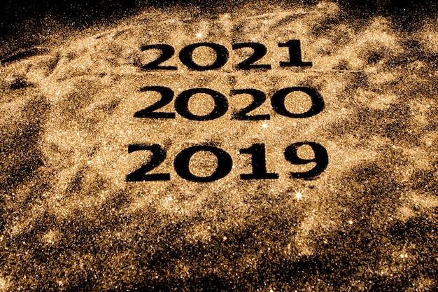 Schöne funkelnde goldene zahlen von 2019 bis 2020 auf schwarz