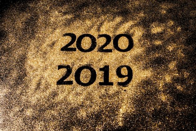 Schöne funkelnde goldene zahlen von 2019 bis 2020 auf schwarzem hintergrund für design, guten rutsch ins neue jahr-konzept