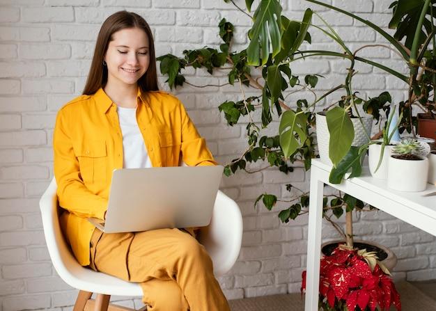Schöne gärtnerin, die an ihrem laptop arbeitet