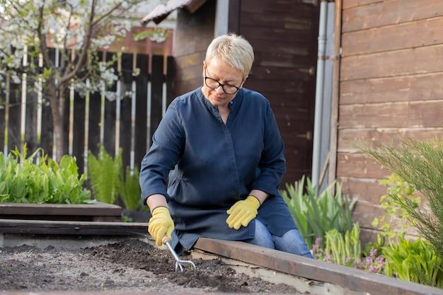 Schöne gärtnerin entfernt unkraut mit hacke aus dem garten und kultiviert erde