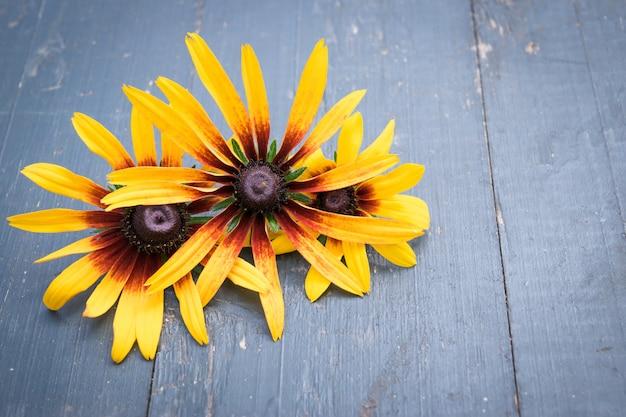 Schöne gartenblumen auf dunklem holztisch