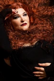 Schöne gealterte frau mit dem starken lockigen roten haar.