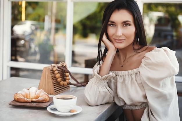 Schöne gebräunte frau in der eleganten bluse, die kaffee an einem café trinkt, das an der kamera lächelt.