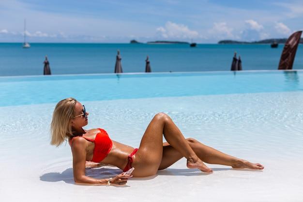 Schöne gebräunte passform kaukasische frau bronze glänzende haut im bikini mit kokosöl durch blauen pool sonnigen tag