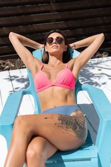 Schöne gebräunte, schlanke frau im bikini im hinterhof, die auf stuhl posiert