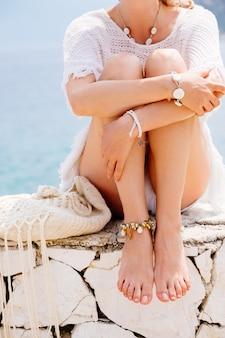 Schöne gebräunte und stilvolle junge frau in den weißen kleidern, die am meer im sonnigen sommertag sitzen. reise- und urlaubskonzept.