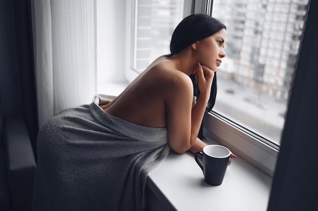 Schöne gelangweilte schlanke brünette frau, die neben fensterfensterbank unter warmer grauer decke zu hause sitzt. selbstisolationsquarantäne während der corona-virus-pandemie. covid19 zu hause bleiben leben retten konzept