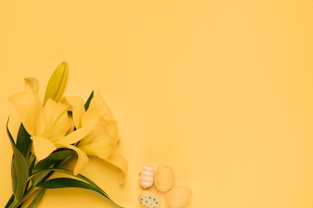 Schöne gelbe lilienblume mit ostereiern auf gelbem hintergrund