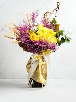 Schöne gelbe rosen des rustikalen blumenstraußes der weizengelbe