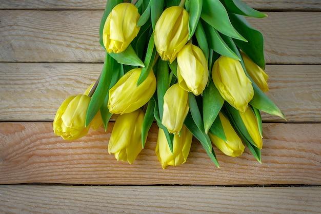 Schöne gelbe tulpen auf hölzernem hintergrund