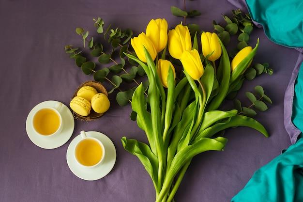 Schöne gelbe tulpen mit heißem getränk und macarons