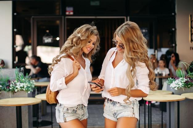 Schöne gelockte zwillinge, die den smartphone draußen steht nahe restaurant halten