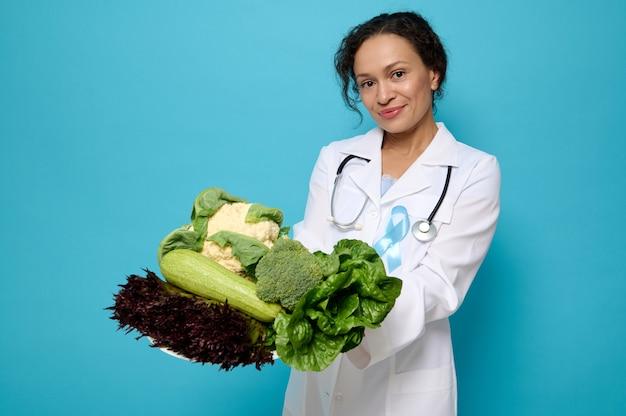 Schöne gemischtrassige ernährungsberaterin in medizinischem kittel und blauem diabetes-bewusstseinsband posiert mit teller gesunder rohkost vor blauem hintergrund mit kopienraum für medizinische werbung