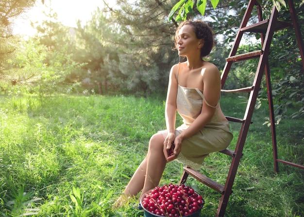 Schöne gemischtrassige frau in einem leinenkleid, die bei sonnenuntergang auf einer leiter neben einem eimer kirschen im obstgarten sitzt. an einem sommertag fallen schöne sonnenstrahlen in den garten