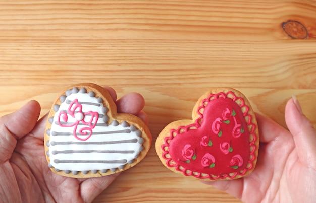 Schöne gemusterte herzförmige kekse in den händen des paares auf holzhintergrund zusammengestellt