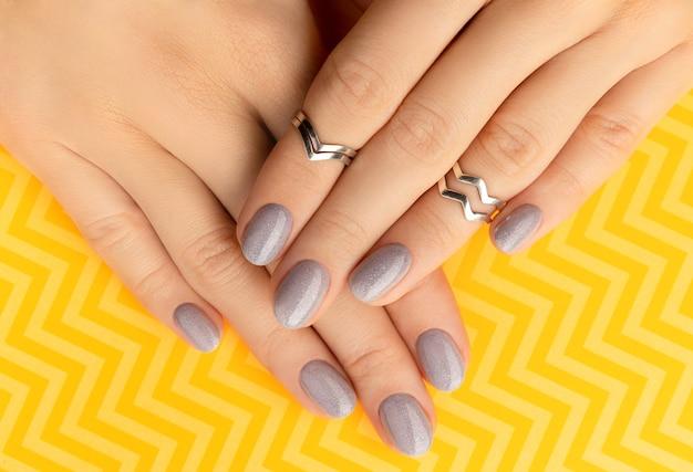 Schöne gepflegte frauenhände mit trendigem nageldesign auf gelb