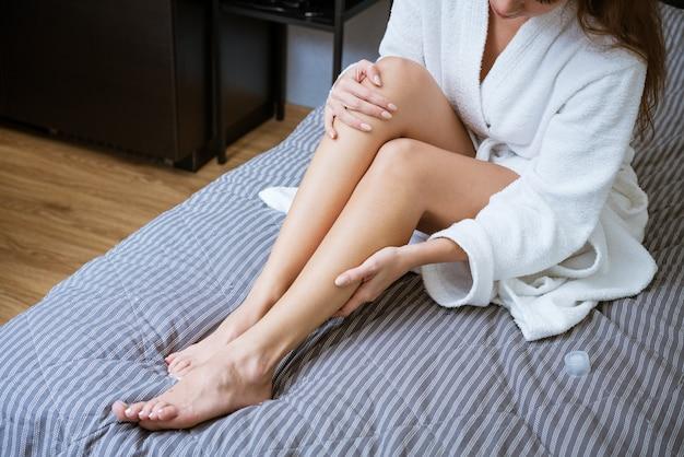Schöne gepflegte füße auf dem bett. fußhautpflegekonzept zu hause
