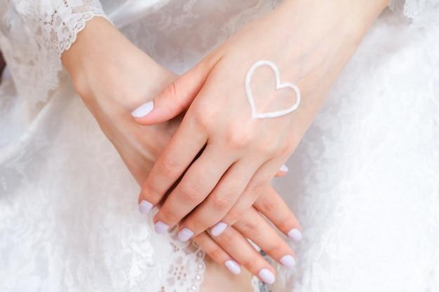 Schöne gepflegte weibliche hände mit herzförmiger creme auf der handfläche.