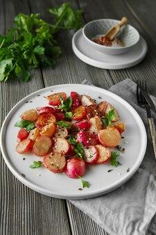 Schöne geröstete radieschen, serviert mit petersilie und sesam in einem teller auf rustikalem holzhintergrund