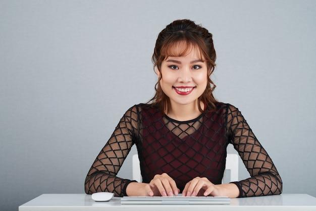 Schöne geschäftsdame, die an der kamera mit ihren armen auf computertastatur lächelt