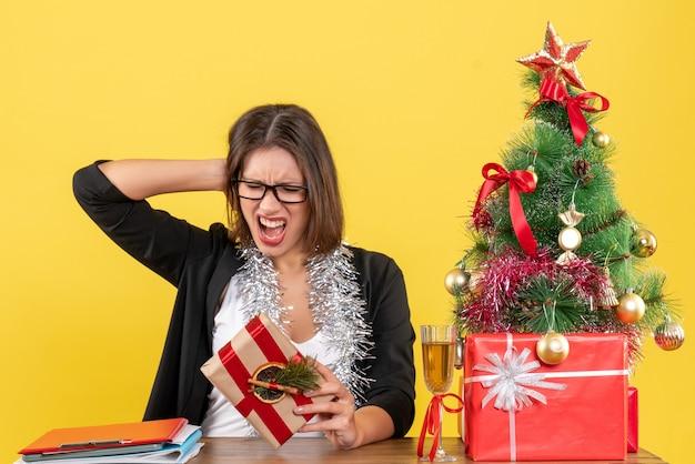 Schöne geschäftsdame im anzug mit brille, die ihr geschenk hält, das emotional an einem tisch mit einem weihnachtsbaum darauf im büro sitzt