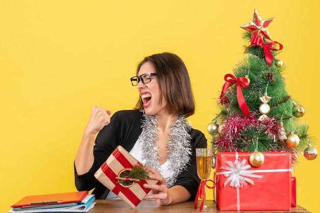Schöne geschäftsdame im anzug mit brille, die ihr geschenk hält, das stolz an einem tisch mit einem weihnachtsbaum darauf im büro sitzt