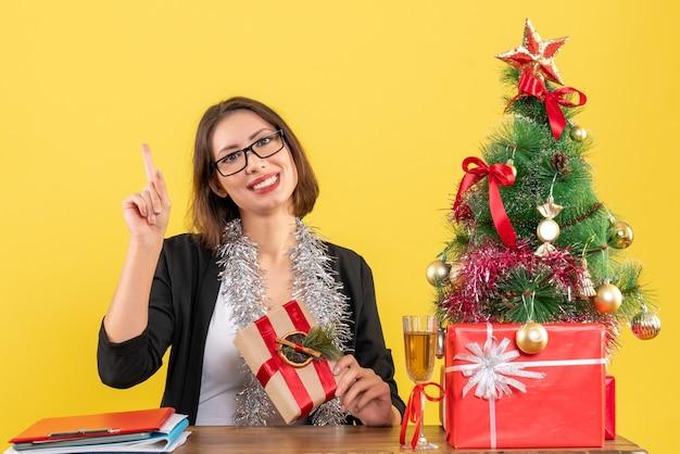 Schöne geschäftsdame im anzug mit den gläsern, die oben zeigen und an einem tisch mit einem weihnachtsbaum darauf im büro auf gelb sitzen