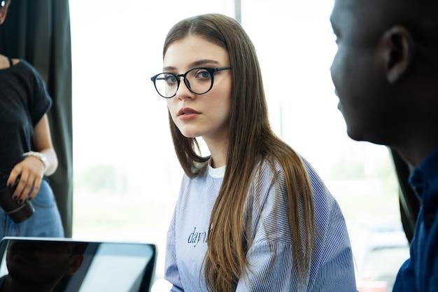 Schöne geschäftsdame schaut in die kamera und lächelt, während sie im büro arbeitet.