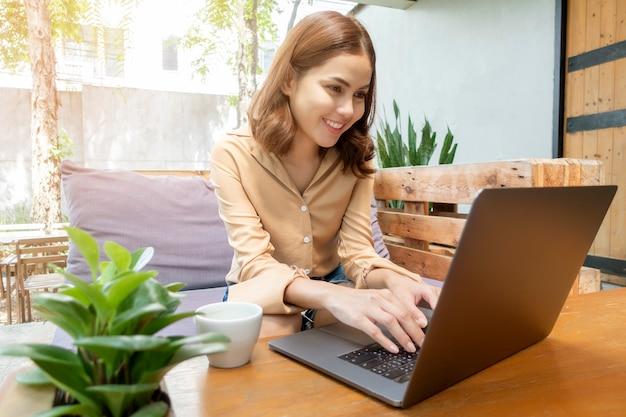 Schöne geschäftsfrau arbeitet mit ihrem laptop in der kaffeestube
