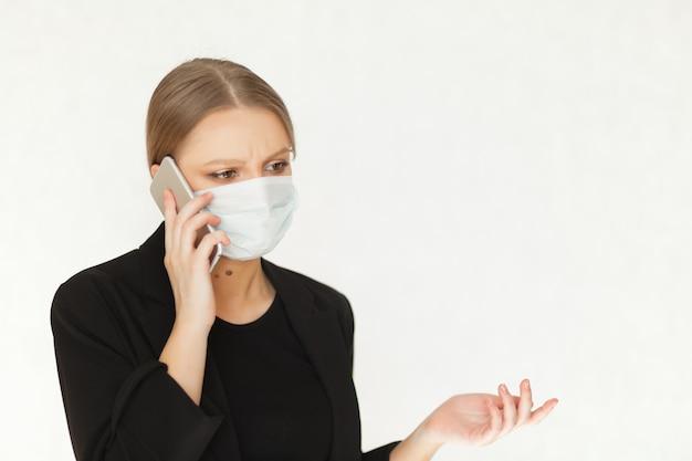 Schöne geschäftsfrau der frau in der medizinischen schutzmaske gegen viren, die am telefon sprechen. vorsichtsmaßnahmen während einer pandemie.