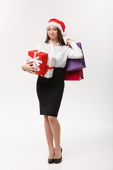 Schöne geschäftsfrau des weihnachtskonzepts, die einkaufstaschen und geschenk mit kopienraum hält