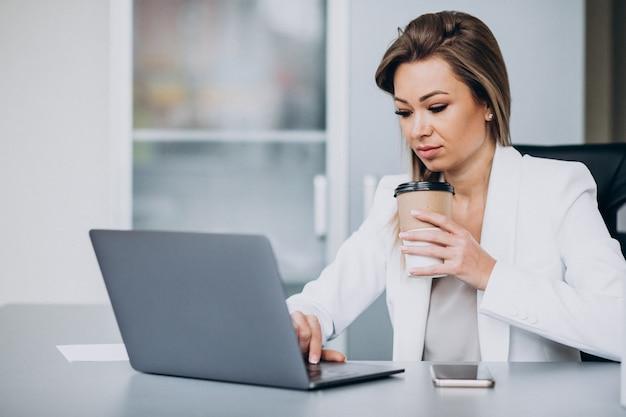 Schöne geschäftsfrau, die am computer im büro arbeitet und kaffee trinkt