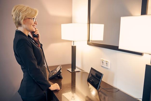 Schöne geschäftsfrau, die am telefon spricht und lächelt, während sie mit tablet-computer am tisch steht und in den spiegel schaut