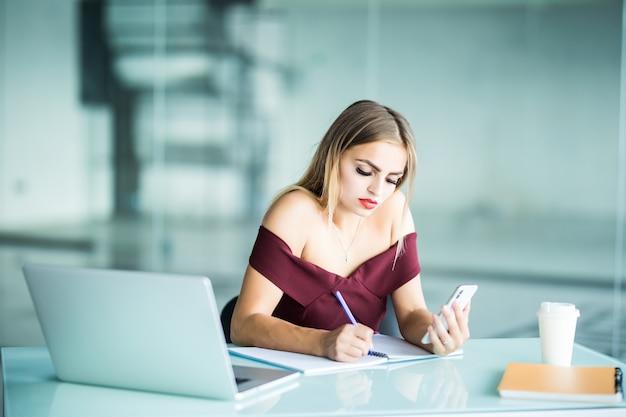 Schöne geschäftsfrau, die an ihrem schreibtisch im büro sitzt