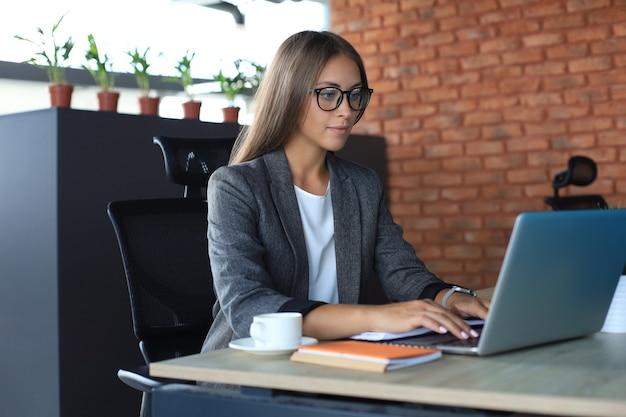 Schöne geschäftsfrau, die an laptop im büro arbeitet.